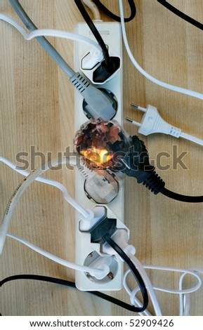 Fire in overloaded power strip. European style connectors. - stock photo