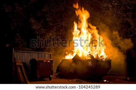 Fire in the city night: burning trash container - stock photo