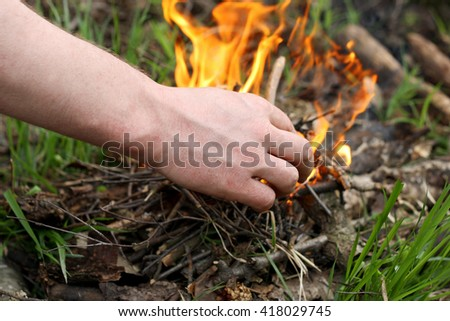 Fire in the forest. The image of a hand of a man who kindles a fire among the grass in the forest. - stock photo