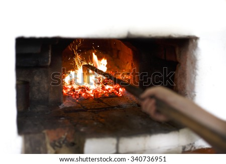 fire in the Russian traditional stove. Stir the coals in the stove with a poker, selective focus