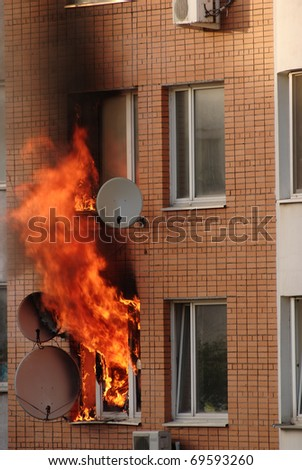 fire in the window of building - stock photo