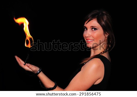 fire juggler woman with flame over dark background - stock photo