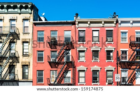 fire laddesrs at beautiful colorful house facades downtown in New York - stock photo