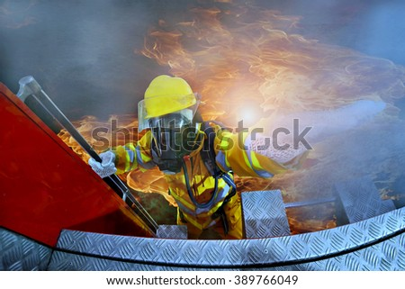 Fire man on top view in action on fire truck. - stock photo