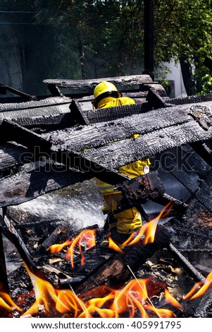 fire man working on damage wood house for fighting fire. - stock photo