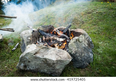 fire outdoors. Firewood burning in big fire. Camping. Enjoying the warmth of the fire - stock photo