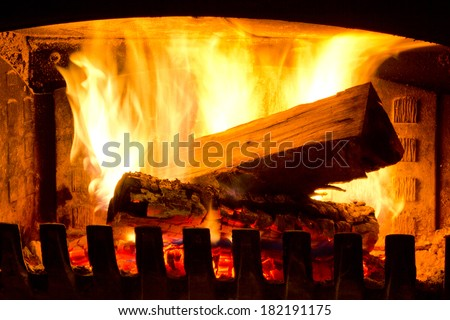 Fire place detail of a fire burning inside. - stock photo