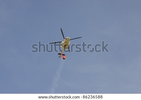 Fire rescue helicopter with water bucket - stock photo