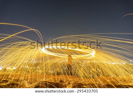 fire spinner on city light background - stock photo