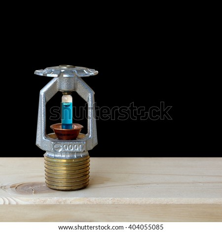 fire sprinkler with fire on wooden background. - stock photo