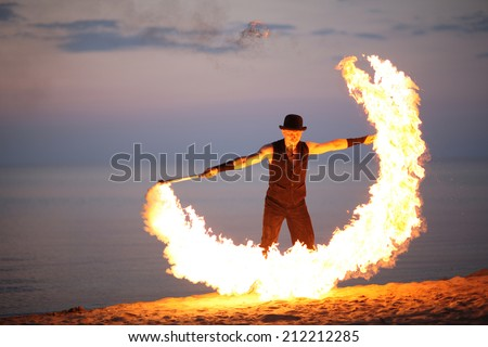 Fire torch twirling on the beach - stock photo