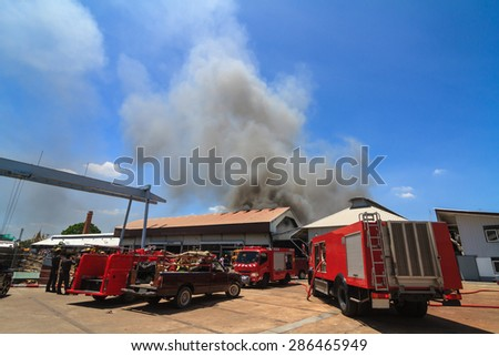 Fire truck and burning warehouses with black smoke against blue sky - stock photo