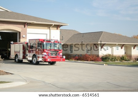 Fire truck in front of fire house - stock photo
