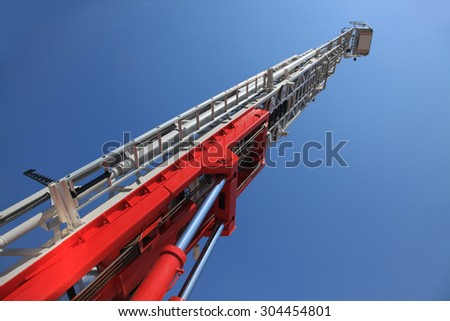 Fire truck ladder leading up into blue sky. - stock photo
