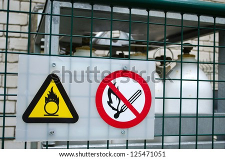 fire warning signs symbol near compressed oxygen gas cylinders. dangerous objects. - stock photo