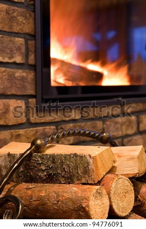 Fire wood against a fireplace - stock photo