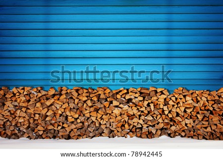Fire wood against blue wall - stock photo