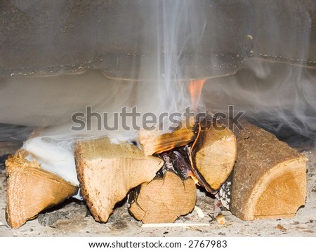 Fire wood burn in a fireplace with a smoke and a flame - stock photo