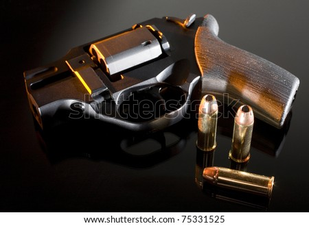 Firearm on glass with ammo just as the sun is going down - stock photo