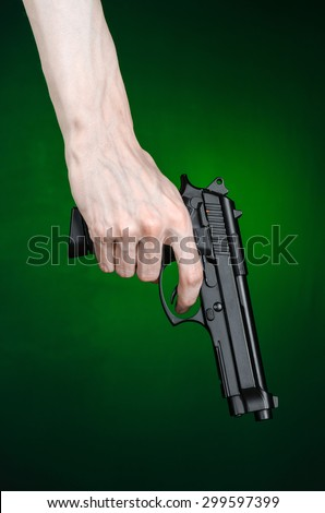 Firearms and murderer topic: human hand holding a gun on a dark green background isolated in studio - stock photo