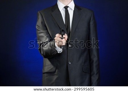 Firearms and security topic: a man in a black suit holding a gun on a dark blue background in studio isolated - stock photo