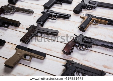 Firearms. Gun. Closeup the gun lies on a wooden white background. - stock photo