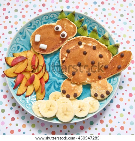 Firebreathing dragon shaped pancakes with peaches, banana and kiwi