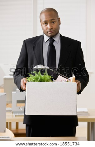 Fired businessman sadly packing personal desk items in box