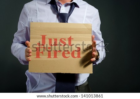 fired employee holding just fired sign in hand - stock photo