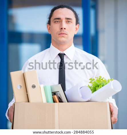 Fired frustrated man holding box with files ar office. - stock photo