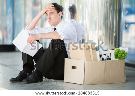 Fired frustrated man in suit sitting near office. - stock photo