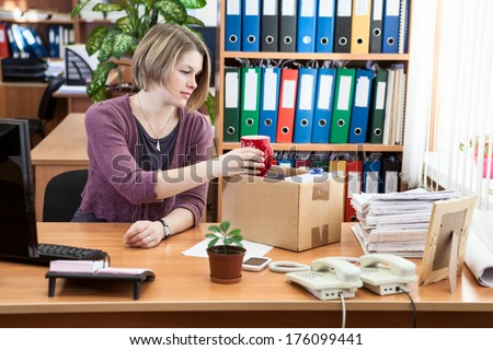 Fired woman collecting things in cardboard box in the workplace - stock photo