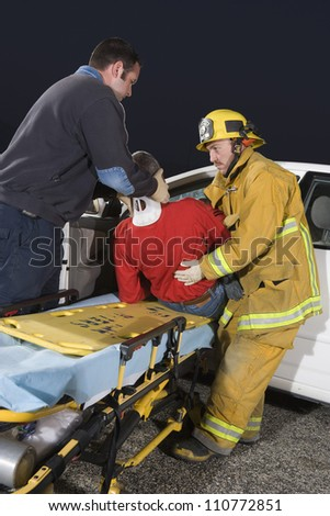 Firefighter and doctor taking out victim from damaged car - stock photo