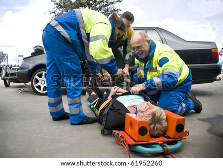 firefighter and paramedic stabilize a victim. - stock photo