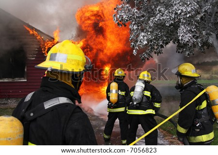 Firefighter at work on an abandoned house in flame - stock photo