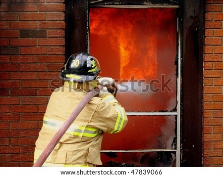 Firefighter attacking a structure fire - stock photo