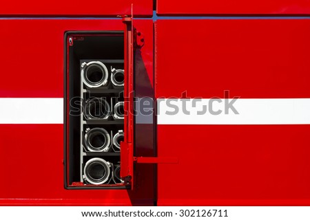 Firefighter car body with fire hoses and pump in compartment with open door, red bodywork with white line of emergency vehicle, rescue service  - stock photo