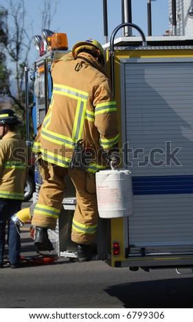 Firefighter climbing on fire truck - stock photo