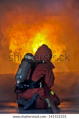 Firefighter fighting a fire during a firefighting training exercise for safety danger,Fire Insurance concept