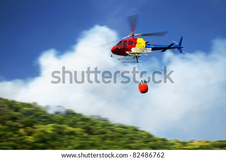 Firefighter helicopter in action flying over a fire in the mountains - stock photo