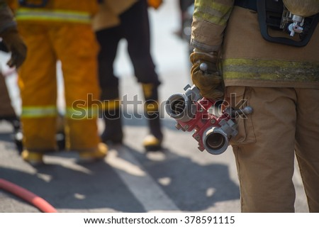 firefighter holding fire hose connection while training - stock photo
