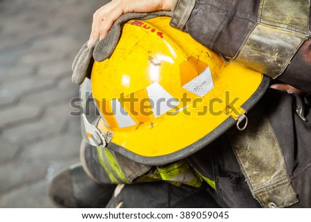 Firefighter Holding Yellow Helmet At Fire Station - stock photo
