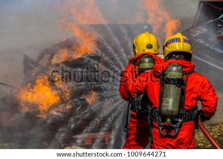 Firefighter in fire fighting operation, Firefighter using extinguisher and water from hose for fire fighting.