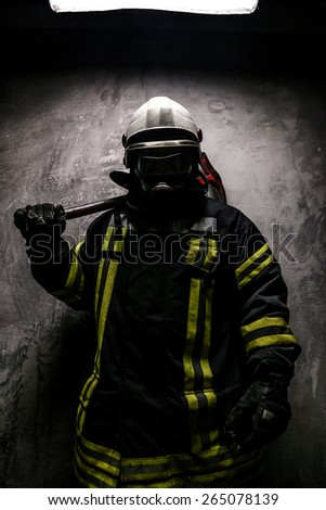 Firefighter in oxygen mask and axe on grey background. - stock photo