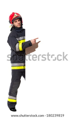 Firefighter in red helmet standing behind big placard and pointing. Full length studio shot isolated on white. - stock photo
