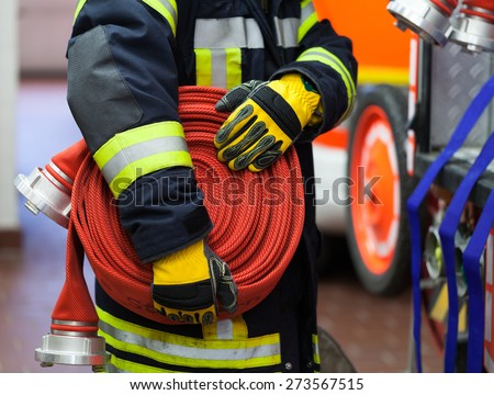 Firefighter in the fire station with hose in the hand - stock photo