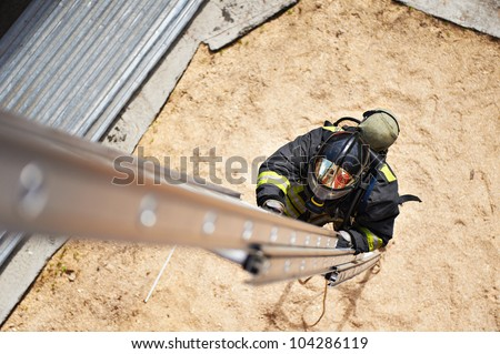 Firefighter in training climb with the fire stairs - stock photo