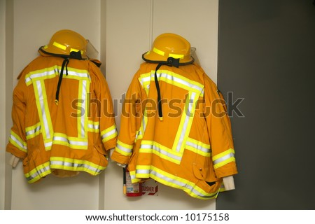 Firefighter jackets and helmets hanging in the fire station - stock photo