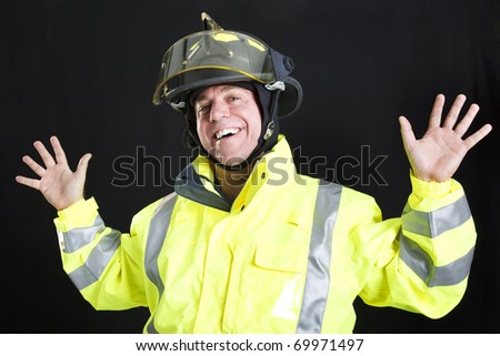 Firefighter lets off steam by goofing around.  Photographed on black background. - stock photo