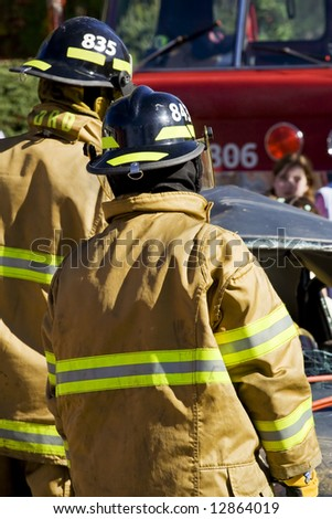 Firefighter looking at a car accident - stock photo